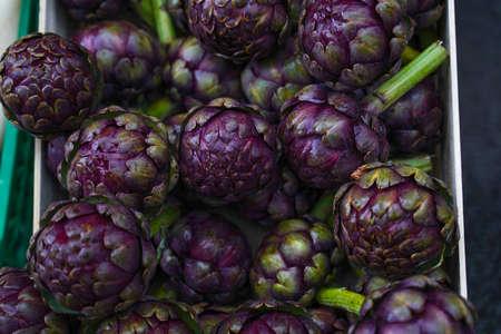 Fresh purple artichokes on the basket in the fruit market. Stock fotó