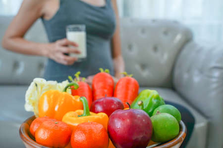 The healthy Asian pregnant young woman with a glass of milk and with many kinds of fruit and vegetable.