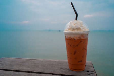 Ice Thai tea on the wooden table and the sea in the background. Imagens