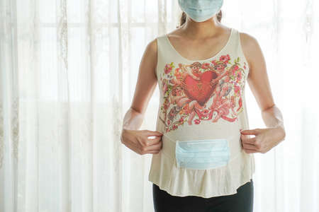 A pregnant woman wears a surgical mask to protect a COVID-19 (Coronavirus) and PM 2.5 and show a surgical mask on the abdomen to prevent infection to the fetus.