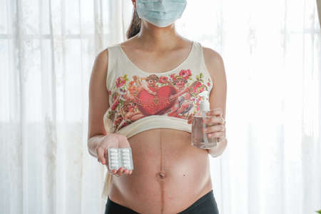 A pregnant woman wears a surgical mask to protect a COVID-19 (Coronavirus) and PM 2.5 and hold the alcohol gel and medicine tablet. Prevent infection to the fetus concept.