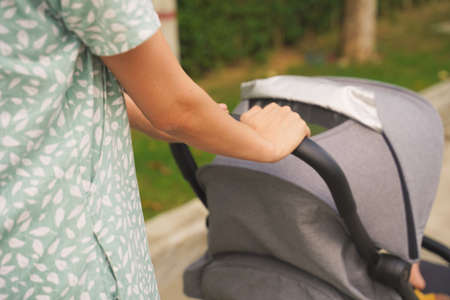 The hand of a mother with the baby stroller in the park.