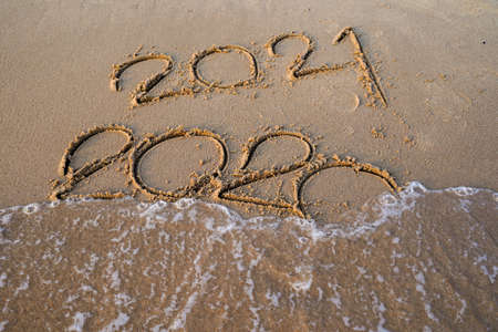 Happy New Year 2021 concept, 2021 number lettering on the sea beach, wave and golden light of sunset.
