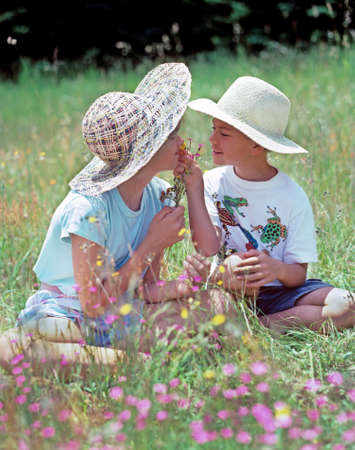 ei: A young boy and girl wearing straw hats are sitting in a field of wildflowers on a sunny day  They are shareing a small bouquet of wildflowers and are smiling at each other  The girl is smelling the bouquet held by the boy  They are between the ages of ei
