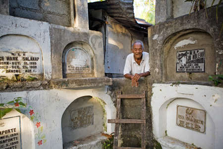 Bacolod City, Philippine Islands, March 2, 2012 - Homeless elderly Filipino man living among stacked concrete tombs in a cemetery. Stock Photo - 14541667