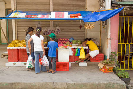 Bogo City, Philippine Islands, April 15, 2012 - Family shopping at an open market stall while owner sleeps. Stock Photo - 14541671