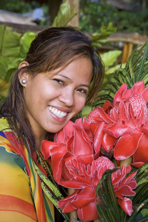 Asian woman from the Philippine Islands with red ginger lilies. photo