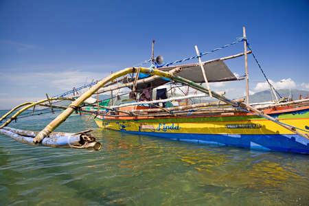 Subic Town; Subic Bay; Philippine Islands - 8102011 - Filipino fishermen aboard their outrigger canoe which is also called a pumboat or bangka. Brightly painted colors on the hull distinguish boat. Pontoons are commonly made from thick culms of bamboo,