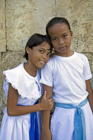 5/16/2012 - Dimiao, Bohol, Philippine Islands - Two young girls in white dresses and blue sashes standing against the limestone block wall of an old cathedral, hugging and posing for a portrait. Stock Photo - 14721159