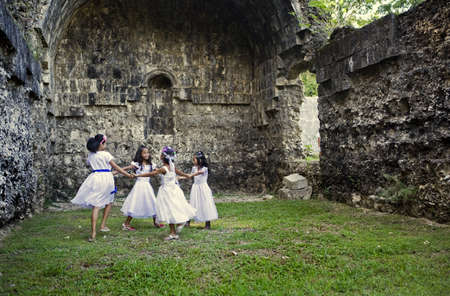 5162012 - Dimiao, Bohol, Philippine Islands - Four young Filipino girls wearing white dresses holding hands dancing in a circle within the Ruins of Ermita, a coralline limestone structure built during the Spanish Regime.