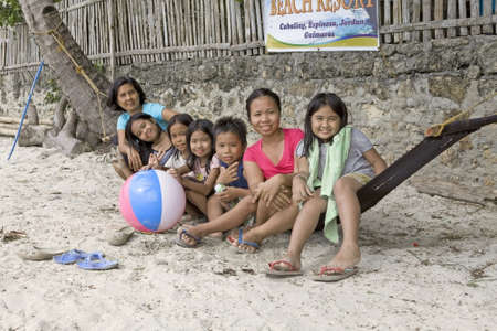 A portrait of seven smiling, friendly Filipino extended family members sitting on a hammock seaside on the beach playing with a beachball, one adult woman, five young children and one teenage girl. Guimaras Island, Philippines.