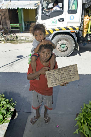 Aeta man, holding a sign in Tagalog language, and his child begging for money at a public market in the Philippine Islands. Stock Photo - 16769494
