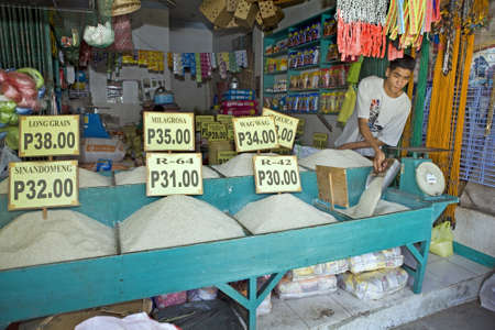 A Filipino man at a public market in the Philippine Islands scoops and measures white rice, a staple food item throughout the country. Stock Photo - 16769519