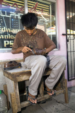 Filipino teen boy cobbler fixing a pair of leather shoes in the Philippine Islands. Stock Photo - 16769495