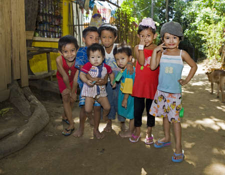 A group portrait of seven cute Filipino children, boys and girls, who play together the older ones look after the young ones.