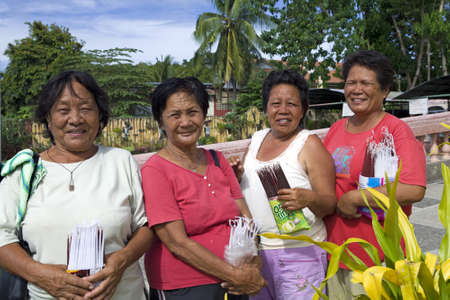christian women: April 2012 - Bogo City, Panay, Philippine Islands - Four senior age Filipino christian women selling devotional candles outside the local Catholic church in Bogo City, Panay, Philippine Islands.