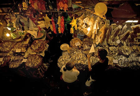 fish vendor: Dried fish vendor and customer doing business at a night market in the Philippine Islands.