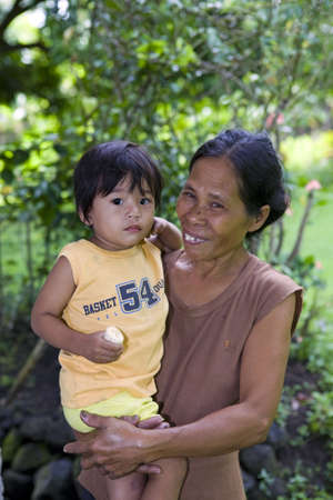 Portrait of a Filipino grandmother holding her baby grandson, live in a rural village home near Legazpi City, Philippine Islands.