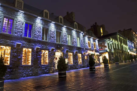 Night scenic of an old, historic stone building with colorful Christmas lighting in the windows - Place Jaques Cartier, Montreal, Quebec, Canada.