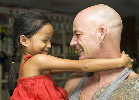 Caucasian man and beautiful, young Filipino girl hugging and smiling at each other  Stock Photo - 16747658