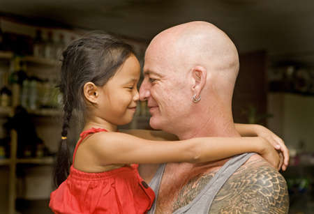 Caucasian man and a beautiful, young Asian Filipino girl touching noses and smiling  Stock Photo - 16747661