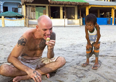 Caucasian man sitting on a beach in the Philippine Islands eating a balot, fermented duck egg, while a young, Filipino boy watches with curious, unbelieving eyes and look on his face. photo