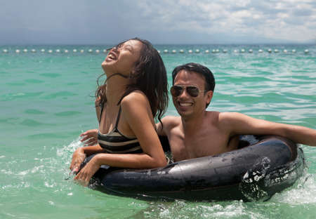 A teenage Filipino girl and her male cousin laughing and enjoying themselves playing with an inner tube swimming in the ocean  photo