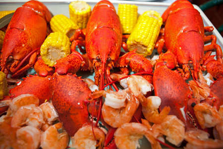 Dinner plate loaded with three red boiled Atlantic lobsters, corn on the cob and shrimp  photo