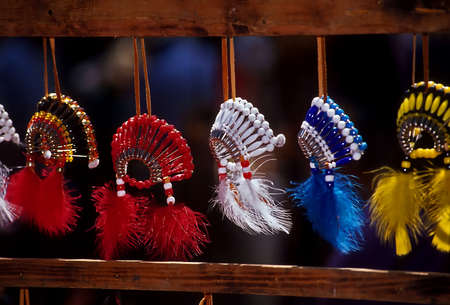 Small native american souvenier headresses, war bonnets, made of plastic beads and feathers for sale at a powwow  photo