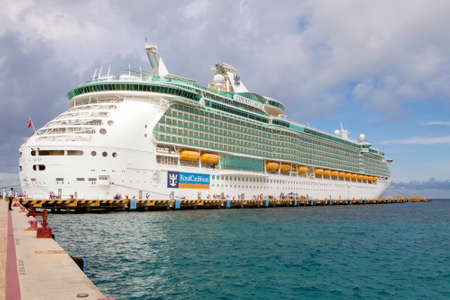 incidental people: Cozumel Mexico  January 14 2015: Liberty of the Seas a Freedomclass luxury cruise ship takes on passengers returning from shore excursions January 14 2015 in Cozumel Mexico. Liberty of the Seas is the secondlargest cruise liner in the world.
