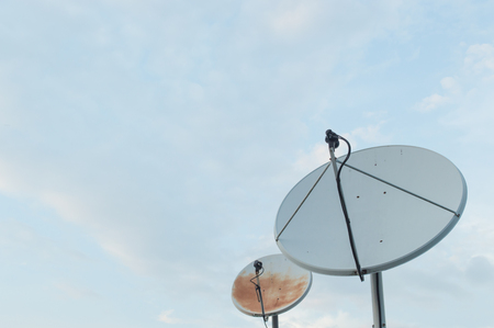 Old rusty old white satellite dishes through use  on sky background Stock Photo
