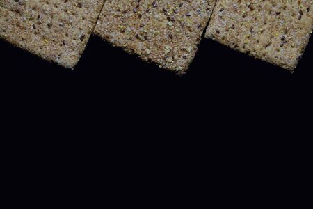 Seeds and cereals in square breads, on dark background