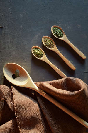 Natural light streaming through the kitchen window, three small spiced spoons and a larger heart-shaped one on a rustic table Stock fotó
