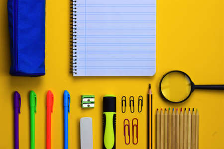 Yellow background. Assorted school supplies various, space for text