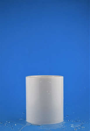 Close-up white porcelain cup, splashed water outline, blue background and space for text