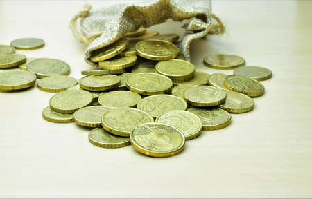 Close up, twenty cents euro coin, outline scattered with a small fabric bag in the background
