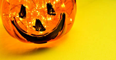 Halloween holiday, glass decoration with small interior lights on yellow background