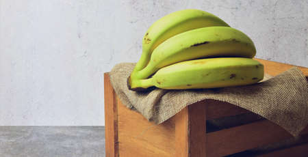 Bananas on rustic cloth and wooden box. Stone background, space for text or idea.