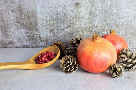 Autumnal presentation, pomegranate fruits with pinecone around it, on stone base