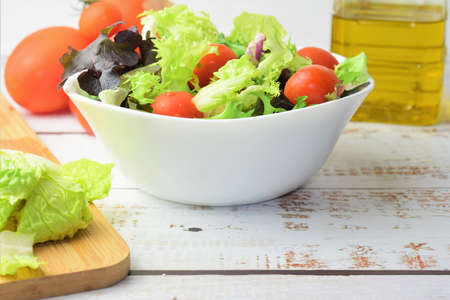 Mixed salad, accompanied by small tomatoes. Healthy contour. Copy space.