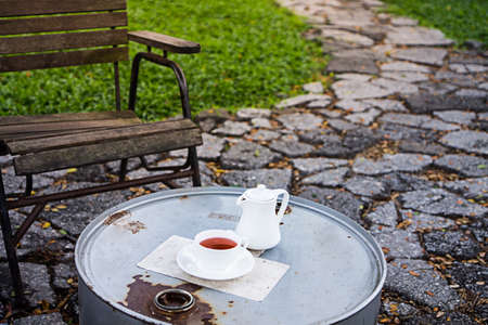mixed drink: Tea on a table outside the garden with a wooden chair and pathway