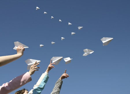 The Children hands send skyward small paper aeroplanes.