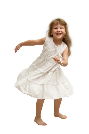 The Small girl in white gown spins, jumps, playing, smiling,  pose on white background.