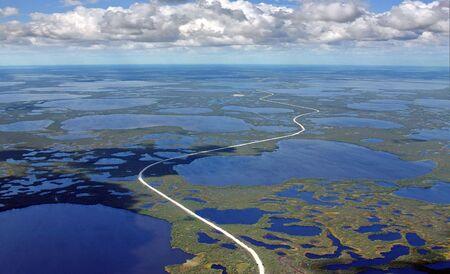 birdseye: West Siberia it is oil region.The Road through marsh on oilfield. The flight a birds-eye view.