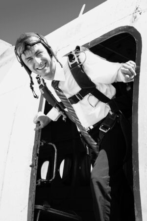 The Mans with parachute stand by the open door of the airplane. He is going to jump downwards.