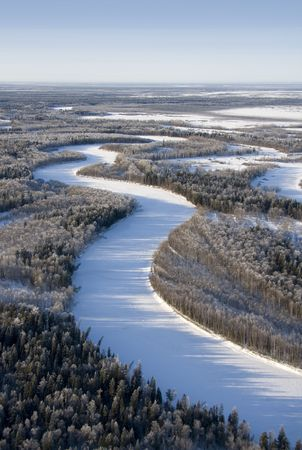The Flight in time of freezing day over snow-clad forest and river. photo