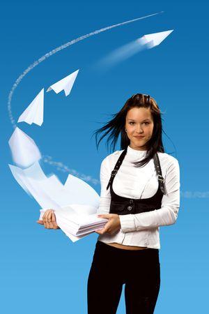 Het meisje houdt documenten partij op haar handen. De wind verhoogt hemelwaarts papieren en zij omhoog geklapt in papier vlieg tuigen.