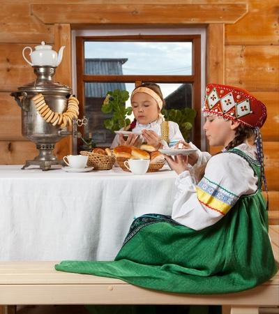 kokoshnik: Two girls drink tea, spun yarn, embroider, chatting and having fun. Stock Photo