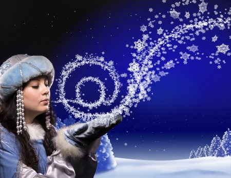 A girl in a fairy dress conjures in Christmas forest. She breath makes snowflakes wich create sign of email and fly out. photo