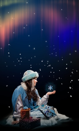 A girl sit in a beautiful to holidays dress under northern lights and stares at his palm hand. She have beautiful snowflake in her palm.